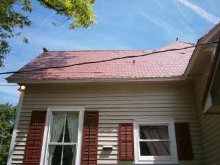 Repair of weaken area of red shingles completed; note the decorative ridge ornaments