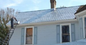 In Winston-Salem, a chocolate brown rusty roof is treated with a strong primer